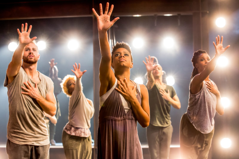 Lead dancer places one hand on his heart and reaches right arm up in praise