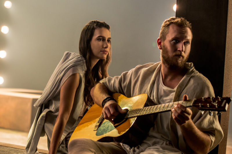Jesus strums his acoustic guitar while Mary Magdalene looks on