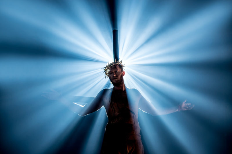 Jesus hanging on a cross wearing a crown of thorns backlit in a white spotlight yet we see his face in anguish